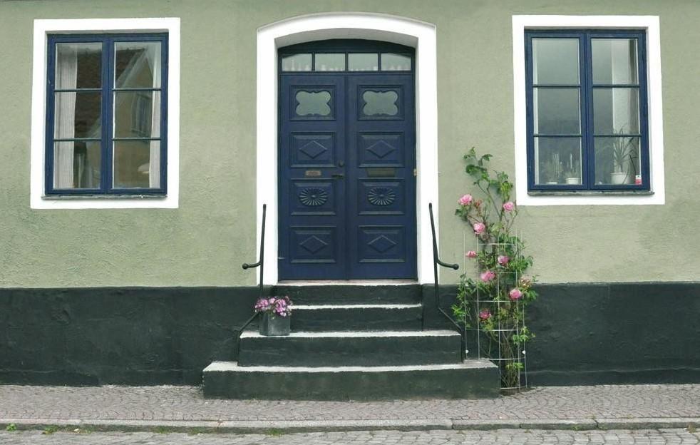 grönt-putshus-med-blå-fönster-och-dörr